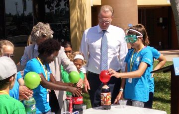 Mayor Kevin Faulconer joins students in an experiment after announcing the expansion of a program offering STEAM workshops.